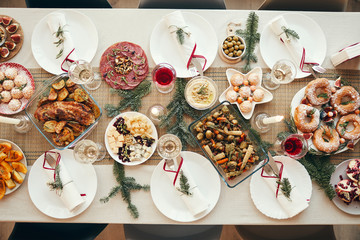 Top view background of beautiful Christmas table with delicious homemade food decorated with fir...