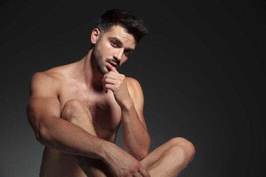 sensual naked man touching lips on grey background