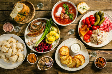 Selection of traditional ukrainian food - borsch, perogies, potato cakes, pickled vegetables, top...