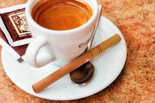 cup of coffee and small cigar on the table. cute bad habits. addiction problem concept