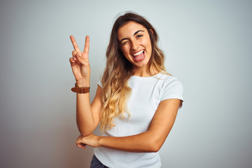 Young beautiful woman wearing casual white t-shirt over isolated background smiling with happy face winking at the camera doing victory sign with fingers. Number two.