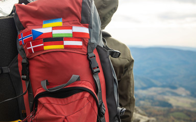travel and hiking life style photography concept picture of different European countries flag stripes on backpack in mountains route environment with blurred background copy space for your text here