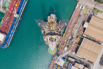 Fototapete - Aerial view of a jack up oil drilling rig and dry dock ship in the shipyard for maintenance.
