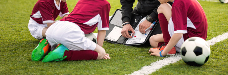 Coach coaching soccer kids soccer team. Youth sports coach using tactics board. Trainer explaining match strategy. Sports soccer education. Three junior players sitting with coach on grass pitch