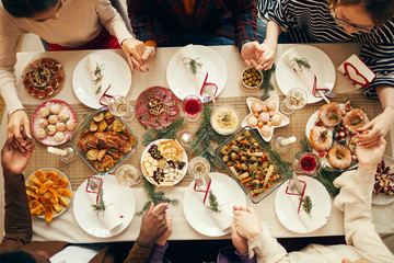 Above view at group of people sitting at dining table on Christmas and joining hands in prayer, copy space