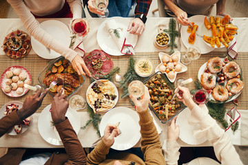 Top view background of people dining at festive Christmas table with delicious homemade food, copy space