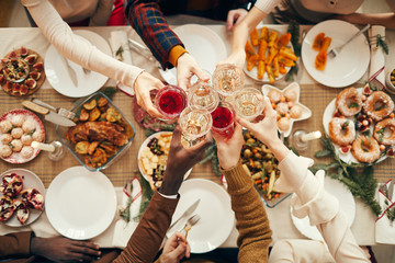 Top view background of people raising glasses over festive dinner table while celebrating Christmas with friends and family, copy space