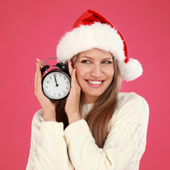 Happy young woman in Santa hat with alarm clock on pink background. Christmas time