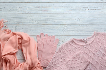 Fototapete - Flat lay composition with warm clothes on white wooden background. Space for text