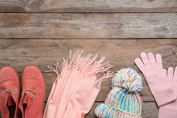 Fototapete - Flat lay composition with warm clothes on wooden background. Space for text