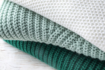 Fototapete - Stack of soft knitted sweaters on table, closeup