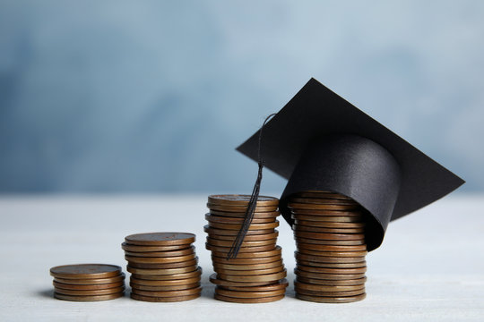 Coins and student graduation hat on white wooden table against blue background. Tuition fees concept