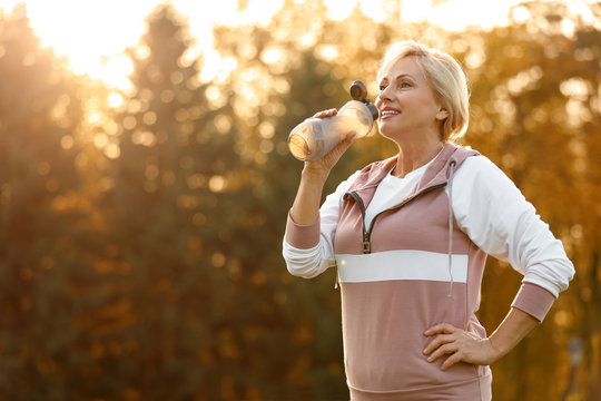 Sporty mature woman with bottle of water outdoors