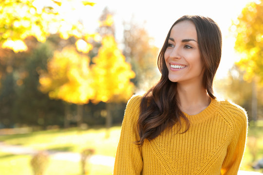 Beautiful woman wearing yellow sweater in park. Autumn walk