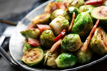 Poster Brussels Delicious Brussels sprouts with bacon in dish on table, closeup