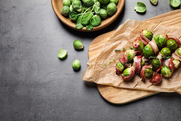 Skewers with Brussels sprouts and bacon served on grey table, flat lay. Space for text