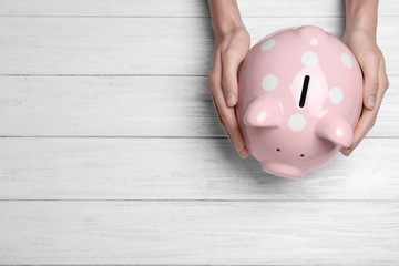Woman holding piggy bank on white wooden table, top view with space for text. Money savings