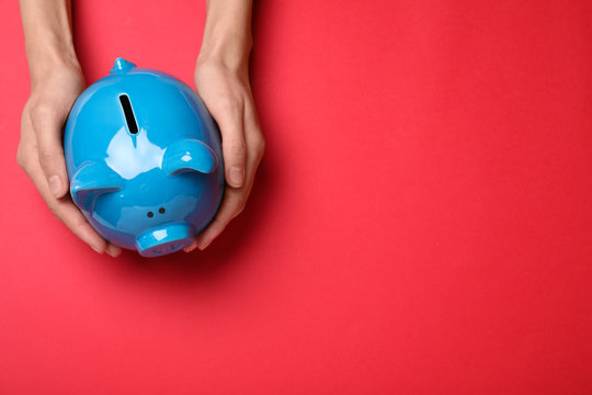 Woman holding piggy bank on red background, top view with space for text. Money savings