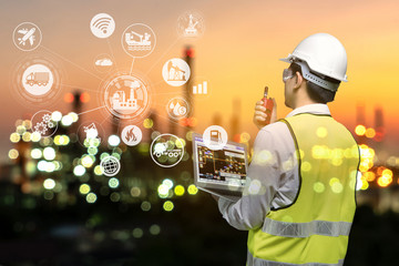 Engineer holding walkie talkie are working order at oil and gas refinery. Industry petrochemical concept image and icon connecting networking using technology.