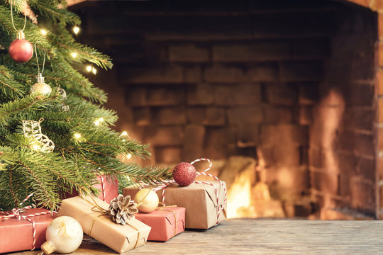 Gifts under the Christmas tree in the room with a fireplace on Christmas eve