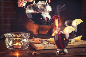 Pouring mulled wine into glasses from a teapot in a room with a fireplace