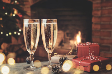 Two glasses with champagne and gifts on a wooden table in a room with a burning fireplace