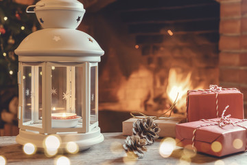 Lantern with a burning candle, gifts on a wooden table in a room with a Christmas tree and a fireplace on Christmas Eve