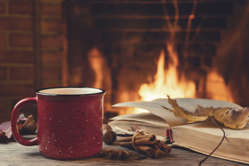 Red mug with hot tea and an open book in front of a burning fireplace, comfort, relaxation and warmth of the hearth concept