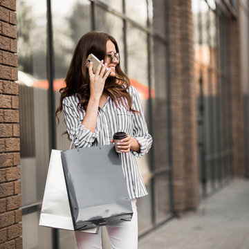 Woman walks after shopping and uses the phone.