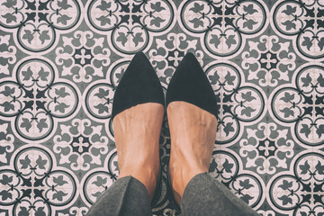 From where I stand first person view perspective of woman standing on tiled floor taking selfie of black suede pointy shoes walking over old fashion ornament pattern tiles in Europe.