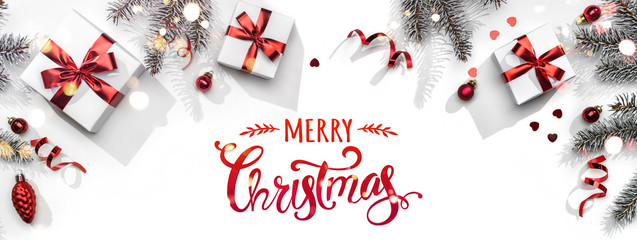 Merry Christmas text on white background with gift boxes, ribbons, red decoration, fir branches, bokeh, sparkles and confetti. Xmas and New Year greeting card, bokeh, light. Flat lay, top view Wall mural