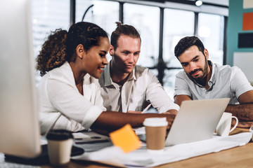 Successful group of casual business discussing and working with laptop computer.creative business...
