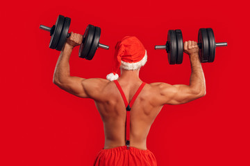 Nude Santa Claus training back with dumbbell