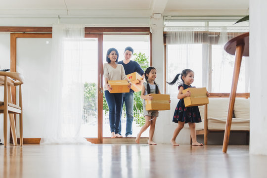 Asian family moving to new home / apartment with many packing boxes