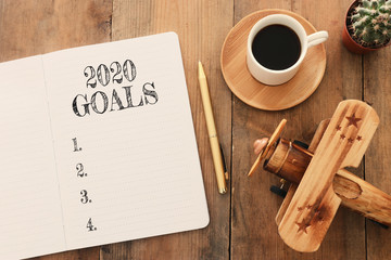 Business concept of top view 2020 goals list with notebook, cup of coffee and old plane toy over wooden desk