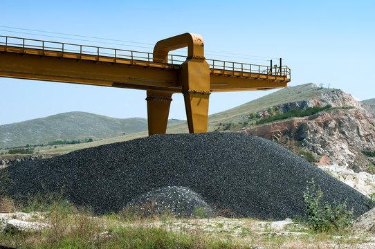 Asphalt pile and crane in quarry