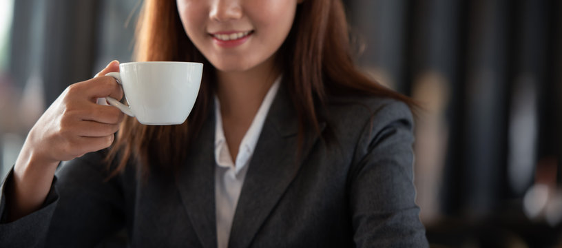 Happy young woman with coffee cup in the morning at restaurant.