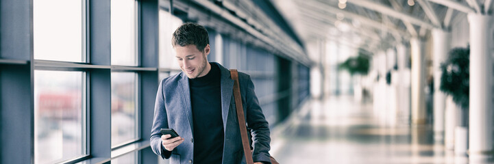 Business man texting on mobile phone at airport on business trip using cellphone texting sms...