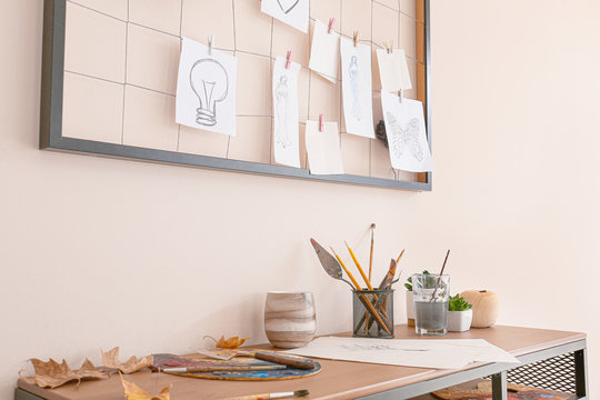 Comfortable workplace with mood board near light wall