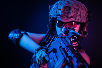 the girl in military overalls airsoft posing with a gun in his hands on a dark background in the haze in neon light