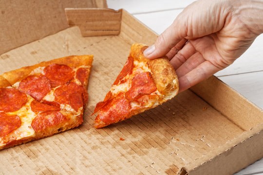 Closeup slice of italian pepperoni pizza in hand and open box with pizza leftovers