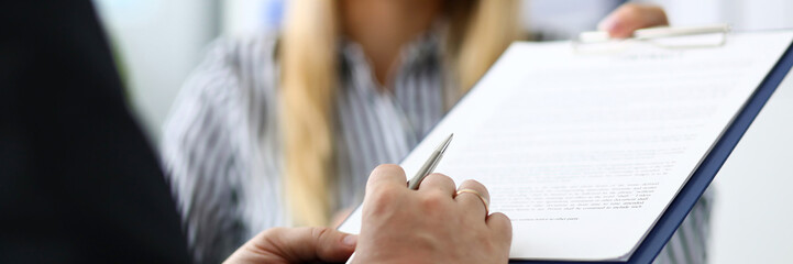 Smiling female real estate agent offering male visitor document to sign clipped to pad close-up