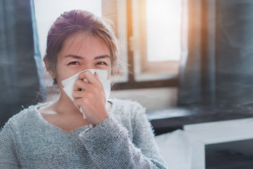 Sick asian woman sneezing on nose with tissue paper because air pollution prevent germs and viruses in symptoms, PM 2.5, selective focus.
