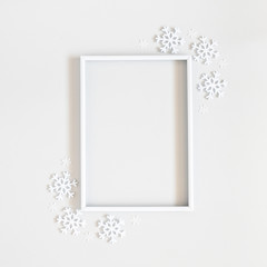 Christmas composition. Photo frame, snowflakes on pastel gray background. Christmas, winter, new year concept. Flat lay, top view, copy space, sguare