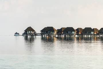 Water bungalows and blue turquoise sea in a tropical paradise island in Maldives