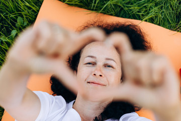 Smiling middle aged woman showing a heart shape from her fingers and looking through it - Image