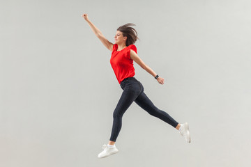 Full lenght of happy beautiful brunette young woman in casual red shirt jumping up in super hero pose and looking forward with toothy smile. indoor, studio shot, isolated on gray background.