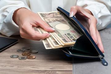 Close up female hand holding Japanese yen 10000 notes