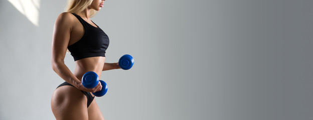 Slim woman with dumbbells.