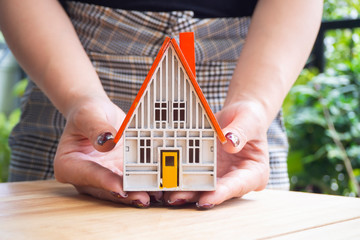 Close up female hand holding house model, concept of housing,property,real estate